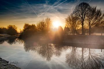 Fluss am Morgen mit aufgehender Sonne im Nebel