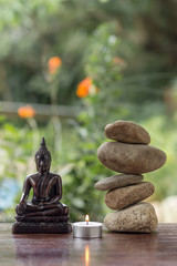 buddha with balanced zed stones and a candle