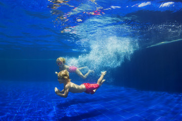 Happy family - funny kids learn to swim, dive underwater with fun. Jump with water splashes in pool. Healthy lifestyle, active people, sports activities, swimming classes on summer holidays with child