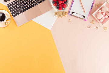 Female home office workplace with laptop, stationery on colorful pink and yellow pastel background. Flat lay of women's office desk. Top view feminine summer bright background.