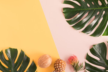 Tropical summer flat lay on yellow background with palm leaf, coconut, pineapple. Top view travel or vacation concept. Summer background.
