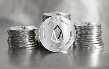 EOS digital crypto currency. Stack of silver coins. Cyber money.