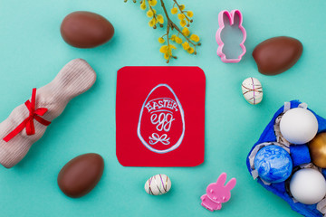 Easter background with sweets and eggs. Picture of egg on red card. Easter symbols and traditions.