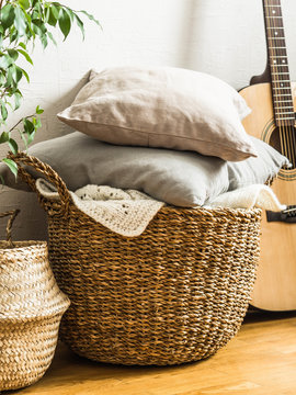 Wicker basket with gray cushions, houseplant and guitar on floor near a white wall