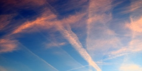 Beautiful vapour trials from aircrafts during an orange sunset sky seen in Germany