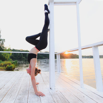 Blonde woman doing supportead handstand on a white wooden lake pier. Yoga nature concept.