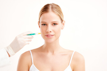 Close-up portrait of young woman having botox treatment