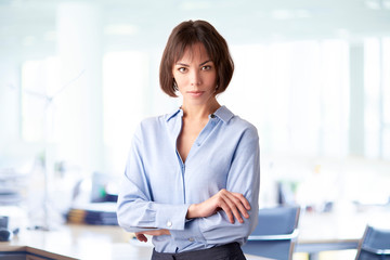 Attracive businesswoman standing with folded arms in the office