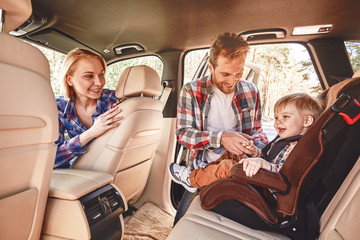 Travel is like an endless university. You never stop learning. Parents playing with their kid inside a car. Family road trip