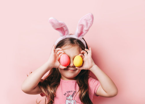 Cute little girl with bunny ears on pink background. Easter child portrait, funny emotions, surprise. Copyspace for text.