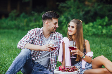 Picnic time. Man and woman in park with red wine. Romantic moments.