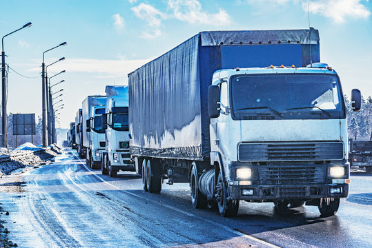 Freight trucks on the road at winter day time.