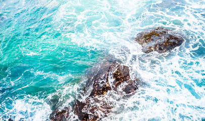Texture of Turquoise sea with spray on stones