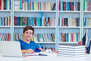 student preparing exam and learning lessons in school library, making research on laptop and browse internet