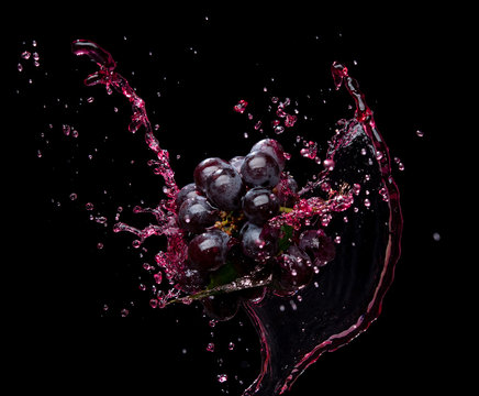 Bunch of grapes with red juice splash isolated on black background
