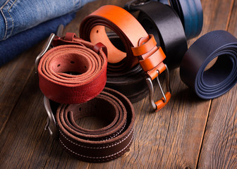 Leather colored belts on a wooden table.