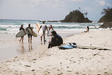ragazzo seduto in spiaggia, con tavola da surf con ragazzi sullo sfondo