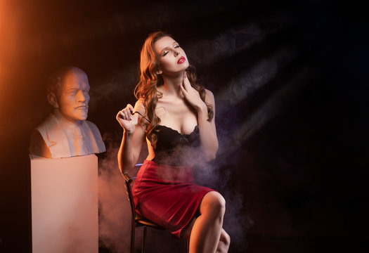 Beautiful sexy leggy busty blonde girl wearing a red skirt and black body sits on a chair at the statue of the communist leader Lenin in theatrical smoke.