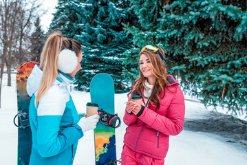 Two girlfriends girls sisters talking to me smiling at the background of snow-covered forest and snowboards. Rest at the resort in cold weather. In the hands of cup with hot coffee or tea.