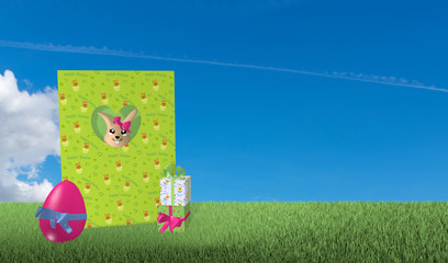 Grußkarte aus der ein Osterhase schaut mit Geschenken und Osterei auf grüner Wiese mit blauem Wolkenhimmel.