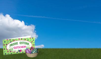 Gutscheinkarte und Osterkorb auf grüner Wiese bei blauem Himmel .