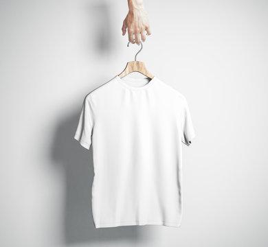Hand holding empty white shirt