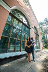 Two people in love stand hugging by large windows in the park and look at each other.