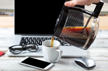 Male hand fulling cup up with coffee with workstation technology in background