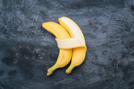 Two bananas isolated on dark background