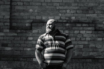 Fat man in the park looks into the frame, a portrait of a man with excess weight.