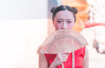 front view of a chinese woman with wooden fan in temple