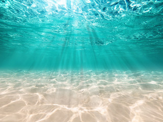 underwater background  deep blue sea and beautiful light rays with sandy floor