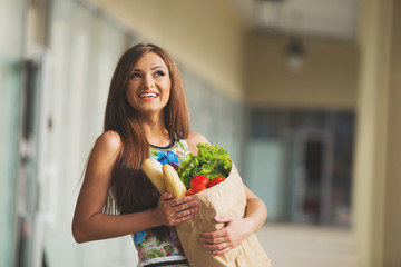 stunning and very beautiful woman in dress with long brown hair holding food in bag near shop