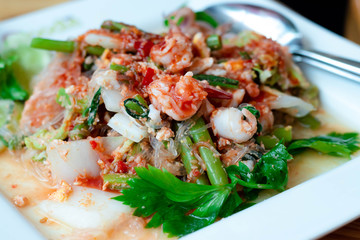 Dry suki Is a fast food popular of thai people dry suki this dish consists of with chinese cabbage shrimp, squid vermicelli and celery all in a white plate.