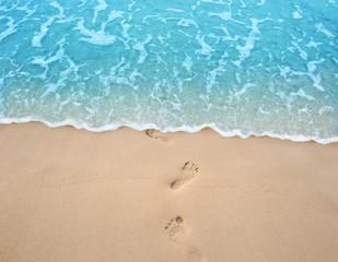 Fototapete - Soft blue ocean wave on clean sandy beach with foot print