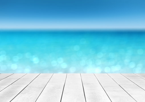 wooden table top with blur ocean background summer concept