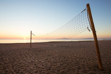 beach volleyball net near sea at sunset