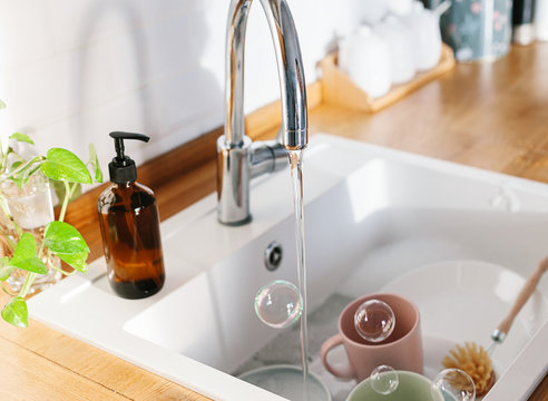 White sink glass soap dispenser bamboo dish washing brush wooden countertop and white ceramic brick tile background