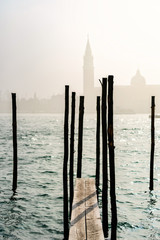 San Giorgio Maggiore church and wooden pier in Venice during a misty/foggy spring day, Venice, Italy.