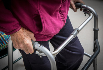 Senior man with disability recovery at home walking frames close-up
