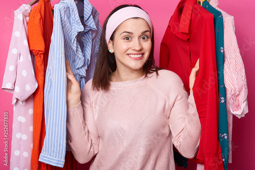 05a69a096f Happy smiling girl stands between hangers with blouses in fashion store. Cheerful  woman visits boutique. Cute lady likes to go to mall. Beautiful young ...