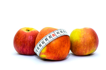Photo isolated on white background apples and measuring tape. Healthy food for weight loss and keeping fit. Tape for measuring the waist and apples.