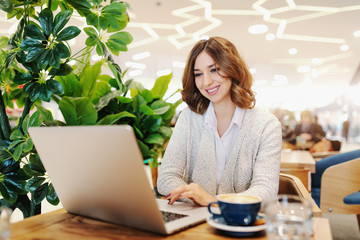 Beautiful businesswoman with toothy smile and brown hair dressed casual using laptop. Cafeteria interior. On desk coffee.
