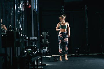 Powerful caucasian woman in sportswear and with pigtail doing exercises in gym barefoot.