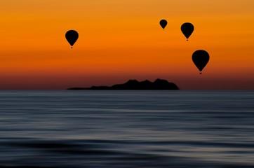 Bellissimo scenario con sagome di mongolfiere in volo sul mare al tramonto
