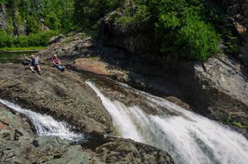 two men sitting near large waterfall