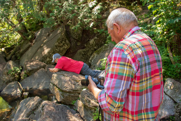 men taking photographs on rocky hill