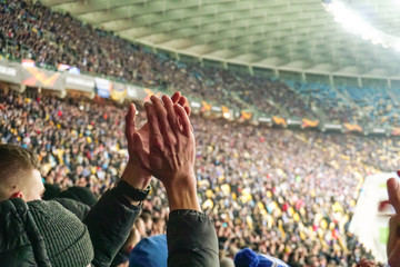 Large crowd of football fans clapping hands, supporting their team. Crowd of sports fans watching game at stadium, slow motion