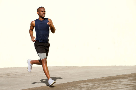 healthy young black man running outside on street