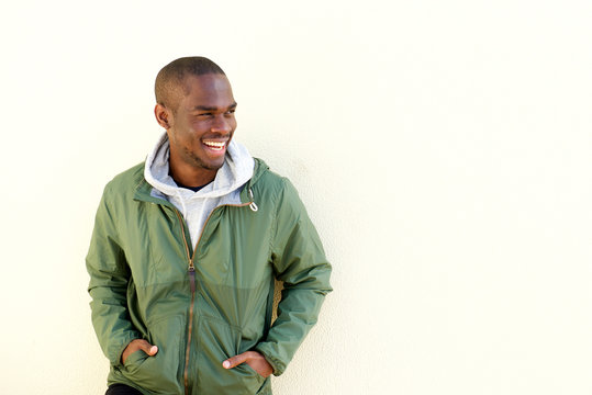 portrait of happy young black man in jacket smiling by wall